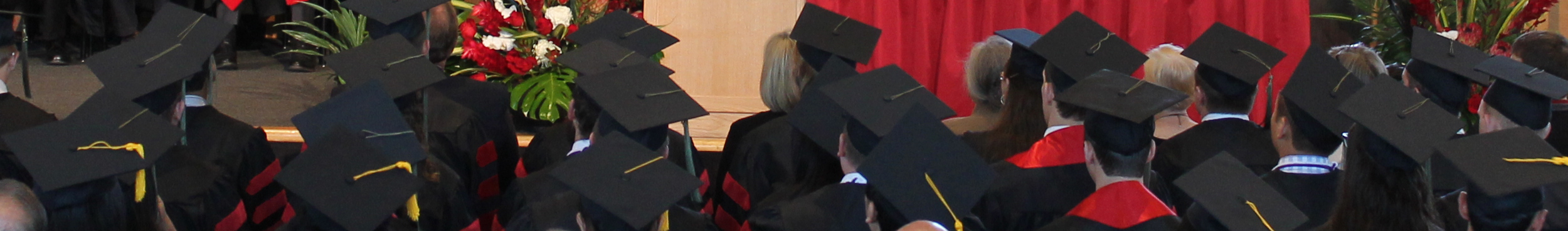 Photograph of students at a convocation wearing graduation caps and gowns.