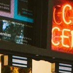 A photo of the fluorescent Copy Center sign lit up above the Copy Center door.