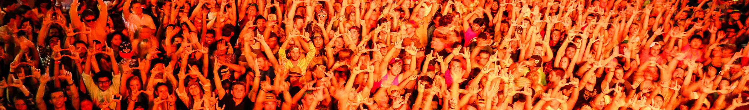 A photo of a dance floor filled with students raising their hands in the Union ballroom.