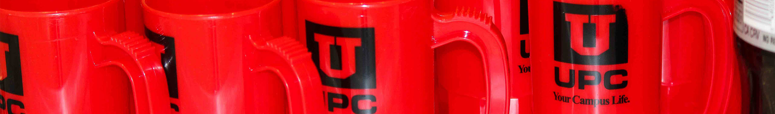 A photo of red, plastic mugs with the UPC logo printed on them.