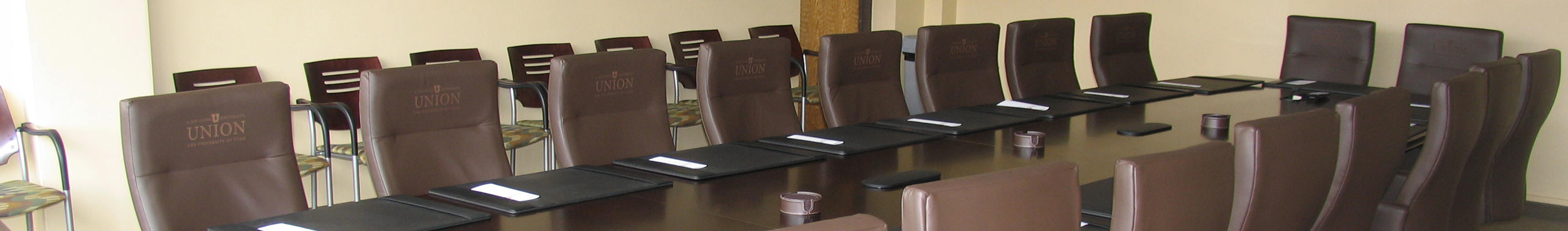 A photo of a board table surrounded by leather chairs.